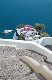 Santorini - The restaurant geared to wedding romantic dinner in Oia (Ia) and the yacht under cliffs Stock Photography