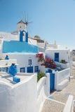 Santorini - schauen Sie zur Windmühle und zur wenig gewöhnlich weiß-blauen Kapelle in Oia Stockbilder