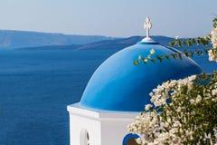 Santorini skyline. Beautiful Santorini landscape with sea, sky and blue church dome in white flowers royalty free stock photos