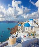 Santorini - spojrzenie typowo błękitni kościelni cupolas w Oia nad kalderą zdjęcia royalty free