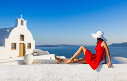 Santorini travel tourist brunette woman in red dress visiting famous white Oia village. Greece, Europe Stock Images