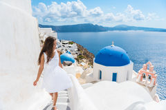 Santorini travel tourist woman on vacation in Oia. Walking on stairs. Person in white dress visiting the famous white village with the mediterranean sea and Stock Image
