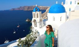Santorini travel tourist woman visiting famous white village with blue domes Oia, Greece. Girl in green dress and sunglasses royalty free stock photo