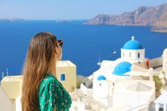 Santorini travel tourist woman visiting Oia, famous white village with blue domes in Greece. Girl in green dress and sunglasses royalty free stock photography