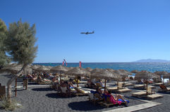 Santorini vacation-the beach and airplane landing Stock Photo