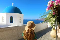 Santorini woman walking in beautiful street of Oia village with flowers and typical blue dome of the church, Santorini, Cyclades. Greece stock photo