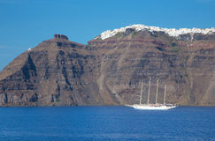 Santorini - yacht and the cliffs under Imerovigli and Scaros castle. Royalty Free Stock Photography
