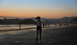 Santos, Brazil. December 05,2018. Girl running on the edge of Sa royalty free stock image