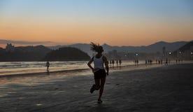 Santos, Brazil. December 05,2018. Girl running on the edge of Sa stock image