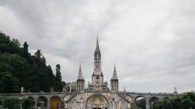 Santuário de nossa senhora de Lourdes sob nuvens, em Lourdes, França imagens de stock royalty free