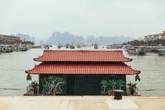 Santuário do estilo chinês na terra com as ilhas longas da pedra calcária da baía do Ha no fundo no verão em Quang Ninh, Vietname fotografia de stock royalty free