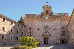 Santuari de Lluc, Mallorca. The entrance to the church in Lluc Monastery - Santuari de Lluc with the statute of Bishop Pere-Joan Campins in the foreground Royalty Free Stock Image