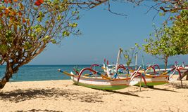 Traditional balinese jukung on Sanur Beach. Sanur is Bali`s oldest upscale resort area and is a mature beach-side town Royalty Free Stock Photo