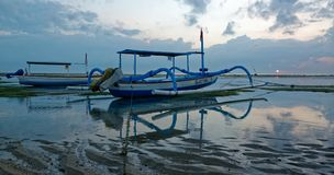 Traditional balinese jukung at sunrise on Sanur Beach. Sanur is Bali`s oldest upscale resort area and is a mature beach-side town Royalty Free Stock Images