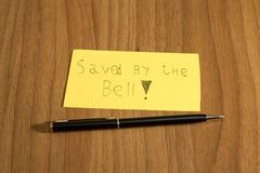 Sanved by the bell, handwrite on a yellow paper with a pen on a. Table composition royalty free stock photos