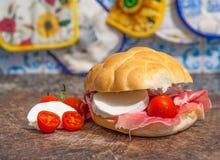 Sanwich con il prosciutto, i piccoli pomodori e la mozzarella Fotografia Stock