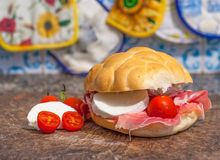 Sanwich with ham, little tomatoes and mozzarella. Macro of sandwich with ham, small tomatoes and mozzarella on a wooden cutting board Stock Photo