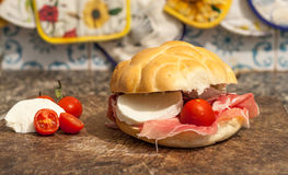 Sanwich with ham, little tomatoes and mozzarella. Macro of sandwich with ham, small tomatoes and mozzarella on a wooden cutting board Stock Images