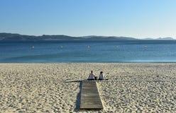 Sanxenxo, Hiszpania Październik 2018 Dwa kobiety są odpoczynkowi i patrzejący widok na plażowym boardwalk Zmierzch, słoneczny dzi fotografia stock