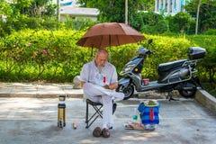 Sanya, Hainan, China - 16 de mayo: 2019: En un día caliente, un chino desconocido en la calle se sienta bajo un paraguas y sueños imagenes de archivo