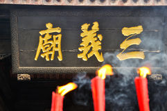 Sanyi Temple Plaque. Three golden Chinese Characters on a Plaque in front of 3 burning candles.Taken in Sanyi Temple,which started in Qing Emperor Kangxi Royalty Free Stock Photo