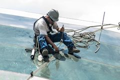 Glass plates on the roof. Sao Paulo, Brazil, January 02, 2017. Worker installs the glass plates on the roof of the Borba Gato station of line 5 lilac of the royalty free stock photography