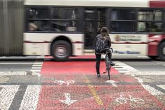 Cyclist awaits the traffic light to cross the road. Sao Paulo, Brazil, June 29, 2016. Cyclist awaits the traffic light to cross the road, stop at the cycle path stock photos