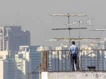 Officials of a building analyze and service television antennas. Sao Paulo, Brazil June 29, 2018. Officials of a building analyze and service television antennas royalty free stock photo