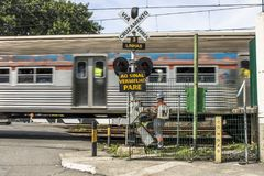 Railroad traffic Light. Sao Paulo, Brazil, March 10, 2017. Level crossing between the street and railroad with traffic light and write to the red stop sign in Stock Photo