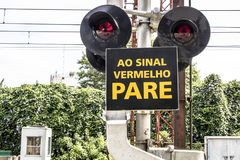 Railway cross. Sao Paulo, Brazil, March 10, 2017. Level crossing between the street and railroad with traffic light and write & x22;to the red stop sign& x22; in Stock Photo