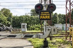 Railway cross. Sao Paulo, Brazil, March 10, 2017. Level crossing between the street and railroad with traffic light and write to the red stop sign in Portuguese Royalty Free Stock Image