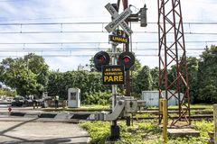 Railway cross. Sao Paulo, Brazil, March 10, 2017. Level crossing between the street and railroad with traffic light and write to the red stop sign in Portuguese Royalty Free Stock Photography