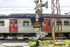 Railway cross. Sao Paulo, Brazil, March 10, 2017. Level crossing between the street and railroad with traffic light and write to the red stop sign in Portuguese Stock Photo