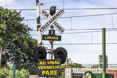 Railroad traffic Light. Sao Paulo, Brazil, March 10, 2017. Level crossing between the street and railroad with traffic light and write to the red stop sign in Royalty Free Stock Image