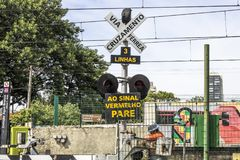 Railroad traffic Light. Sao Paulo, Brazil, March 10, 2017. Level crossing between the street and railroad with traffic light and write to the red stop sign in Royalty Free Stock Images