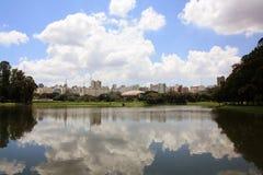 Sao Paulo skyline. Sao Paulo city skyline, over a cloudy sky, reflected on Ibirapuera's park lake Stock Photos