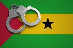 Sao Tomé en de vlag en de politiehandcuffs van Principe Het concept misdaad en inbreuken in het land royalty-vrije stock foto's