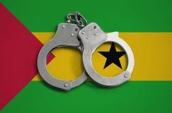 Sao Tomé en de vlag en de politiehandcuffs van Principe Het concept naleving van de wet in het land en bescherming tegen misdaad stock afbeeldingen