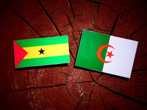 Sao Tome and Principe flag with Algerian flag on a tree stump is Royalty Free Stock Image