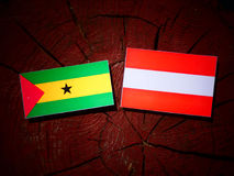 Sao Tome and Principe flag with Austrian flag on a tree stump is Royalty Free Stock Image
