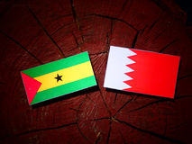 Sao Tome and Principe flag with Bahraini flag on a tree stump is Royalty Free Stock Images