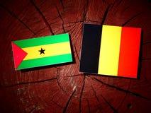 Sao Tome and Principe flag with Belgian flag on a tree stump iso. Sao Tome and Principe flag with Belgian flag on a tree stump Royalty Free Stock Photo
