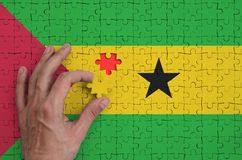 Sao Tome and Principe flag is depicted on a puzzle, which the man`s hand completes to fold.  stock illustration