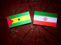 Sao Tome and Principe flag with Iranian flag on a tree stump iso. Lated Stock Images