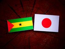 Sao Tome and Principe flag with Japanese flag on a tree stump isolated. Sao Tome and Principe flag with Japanese flag on a tree stump Royalty Free Stock Images