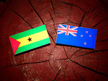 Sao Tome and Principe flag with New Zealand flag on a tree stump. Isolated Royalty Free Stock Image