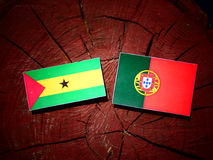 Sao Tome and Principe flag with Portuguese flag on a tree stump. Isolated Stock Photos