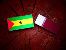 Sao Tome and Principe flag with Qatari flag on a tree stump isolated. Sao Tome and Principe flag with Qatari flag on a tree stump Royalty Free Stock Photo