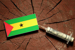 Sao Tome and Principe flag on a stump with syringe injecting money. In flag Stock Photography