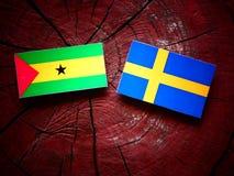 Sao Tome and Principe flag with Swedish flag on a tree stump iso. Sao Tome and Principe flag with Swedish flag on a tree stump Royalty Free Stock Photography